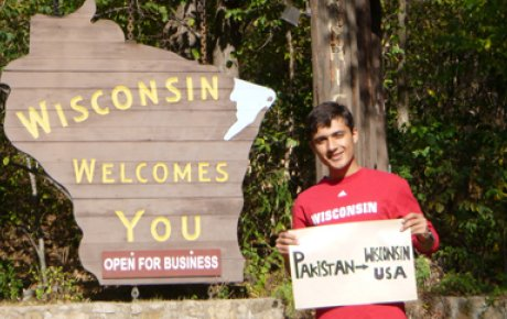 Participant holding sign that says Pakistan to Wisconsin USA