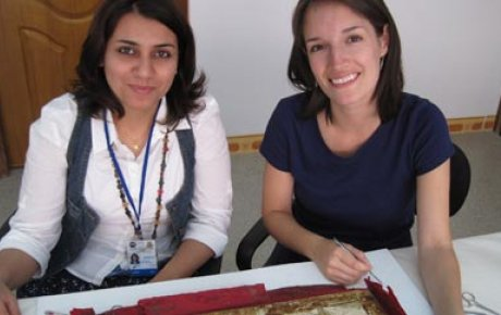 Jessica Arista and IICAH teacher-in-training Zina Ibrahim Kaki remove old fabric from behind an ancient ivory chair-back.