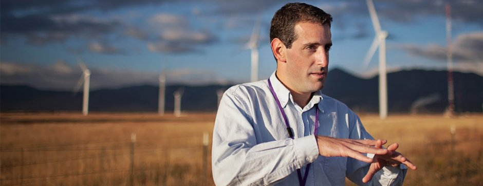 Gabriel Preliasco in front of wind turbines.