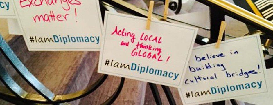 Handwritten signs incorporating the #IAmDiplomacy hashtag