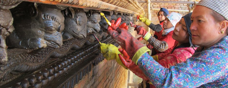 A group of workers cleaning a carved cornice