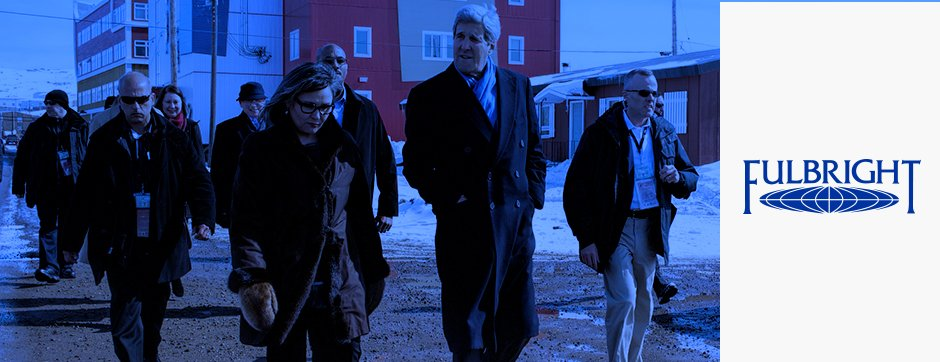 Secretary Kerry walking with a group of people with Fulbright logo to the right