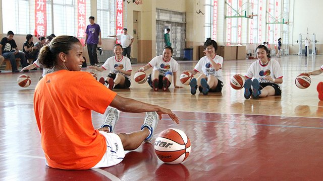 Kiesha Brown dribbles with the girls from Baode Junior High School in China.
