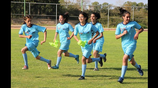 A group of teenage girls run together during a soccer clinic in Morocco.