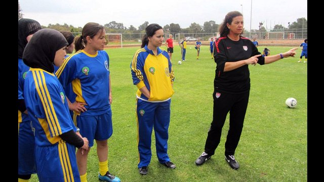 Coach Lesle Gallimore shares a game strategy with a group of Moroccan players.