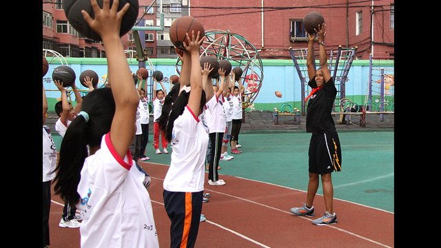 Kiesha Brown teaches ball handling to the girls from Shenhe Migrant Workers Elementary School in China.