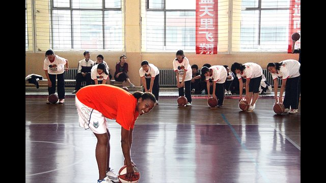 Kiesha Brown does dribble drills with the girls from Baode Junior High School in China.