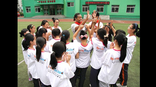 "Tamika Williams ""high fives"" new friends at the Shenhe Migrant Workers Elementary School in China."