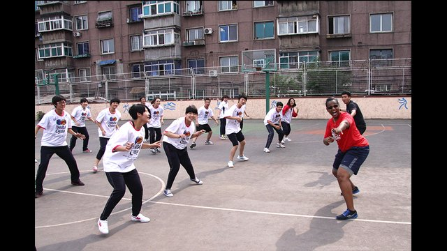 Tamika Raymond practices defensive sliding skills with the girls from Anshan No. 3 High School in China.