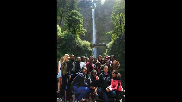The track and field visitors visit a waterfall during their mountain hike in Oregon.