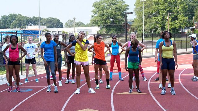 The Caribbean track and field delegation lines up to run sprints during a practice with Arlington Pacer's coach Dustin Sweeney.