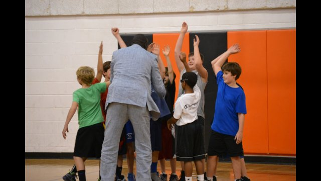 One of the South Sudanese coaches high-fives young American basketball players after a friendly scrimmage.