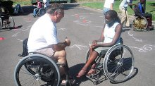 YES student Stella Tiyoy from Kenya meets with a physical therapist and wheelchair user to discuss opportunities to participate in wheelchair sports in the United States.