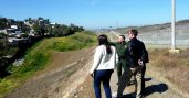 Two people standing on hill look at field a ranger is pointing towards